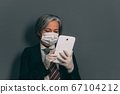 Serious businesswoman in black suit, protective mask and gloves working with digital gadget. Business after quarantine concept. Tinted image 67104212