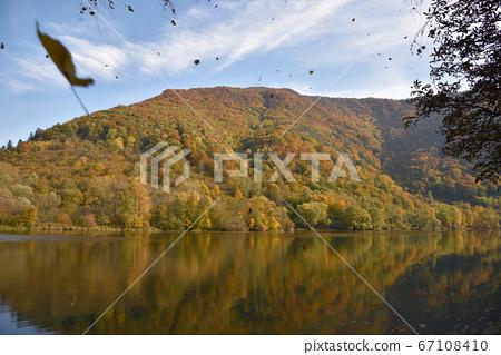在東部河面上,天上白雲窪河畔的美麗森林森林倒映在水面上。 67108410