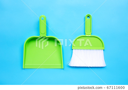 A broom and dustpan on blue background. 67111600