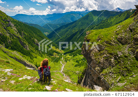 Woman with backpack resting on mountain top, 67112914