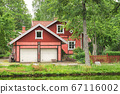 Red wooden traditional scnadinavian house with a garage in front of it 67116002
