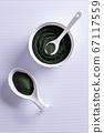 Chlorella or spirulina powder in bowls on white 67117559