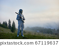 Space traveler standing on grass and holding guitar. 67119637