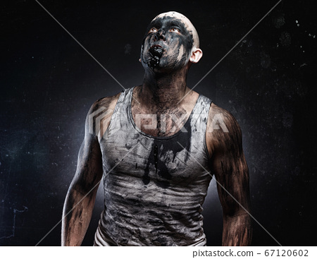 Bald mad man with black muck in the mouth looking up 67120602