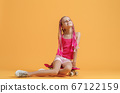 Active young girl in pink shirt and shorts sitting on skateboard over yellow background 67122159