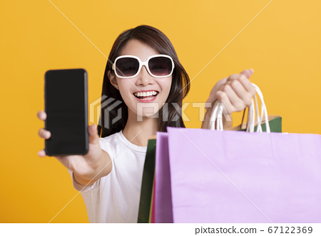 happy young woman showing mobile phone and 67122369