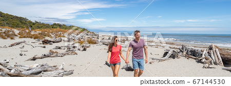 Panoramic banner of Couple walking on beach in New Zealand - people in Ship Creek on West Coast of New Zealand. Tourist couple sightseeing tramping on South Island of New Zealand 67144530