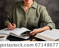 Girl holds phone in hand, writes, study at home. Self education concept. 67148677