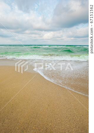 sea tide on a cloudy evening. waves crashing sandy 67151562