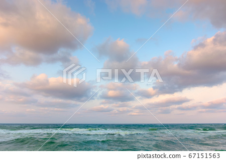 cloudy sunset sea side. waves running the sandy 67151563