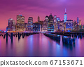 Manhattan skyline at night with varicolored reflections in the water, view from Brooklyn, New York 67153671