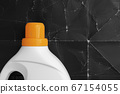 Laundry detergent in a plastic white container with a bright orange screw cap on a background of old crumpled black paper. Recovery and cleaning concept 67154055
