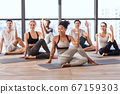 Indoor Group Yoga. Sporty Multiethnic People Practicing Asana Exercises Together In Studio 67159303