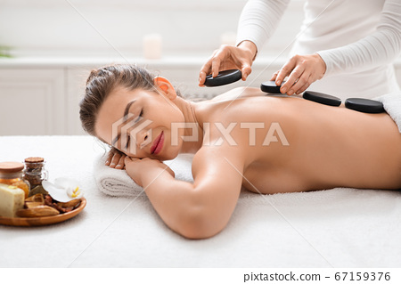Woman enjoying her day at spa, receiving hot stones massage 67159376