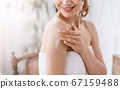 Young woman wrapped in towel applying lotion on shoulder 67159488