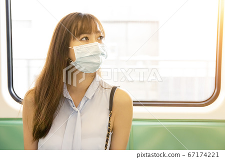 business woman wearing face mask and sitting in 67174221