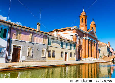 View of the street with canal and colored houses in a small Italian town of Comacchio 67176790