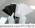 Man holds rubber gloves black and white face masks 67178232