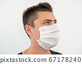 White protective mask on the young guy's face, portrait 67178240
