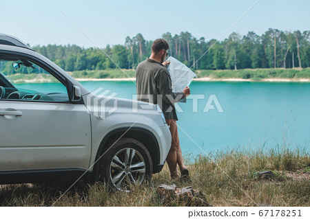 car travel concept man looking on the man at suv car hood lake on background 67178251