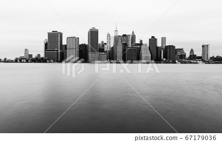 Manhattan skyline in cloudy day, New York skyscrapers reflected in the water 67179036