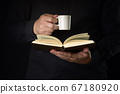 Person reading a book with a coffee cup on a dark 67180920
