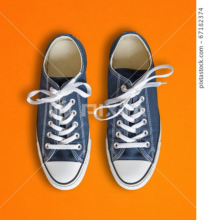 Blue sneakers isolated on orange background 67182374