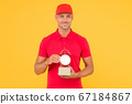 Postman delivery worker. Handsome man red cap hold 67184867