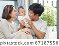 Parents entertaining baby 67187556