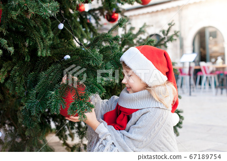 Child is decorating Christmas tree with red ornaments outside. Happy kid is enjoying holidays.