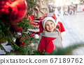 Little kid is smiling under Christmas tree with red ornaments outside. Child girl in santa hat 67189762