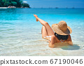 Back view of young woman in straw hat and white bikini relax in turquoise sea 67190046