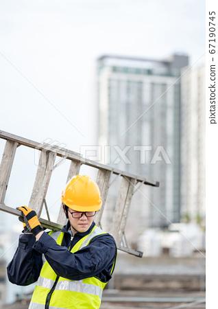 Maintenance worker man carrying aluminium ladder 67190745