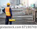 Worker man carrying tool box at construction site 67190749