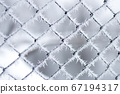 Hoarfrost on metal fence mesh with bokeh background. 67194317
