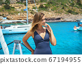 Happy young woman feels happy on the luxury sail boat yacht catamaran in turquoise sea. 67194955