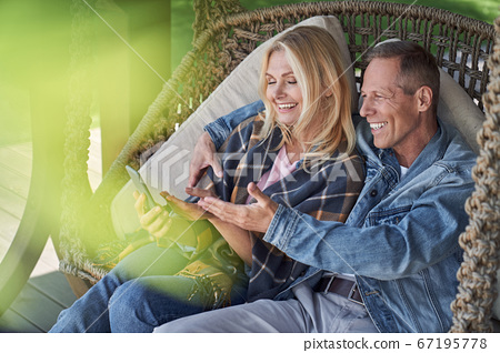 Cheerful couple relaxing with smartphone in open air 67195778