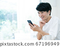 A young man talking while watching a smartphone 67196949