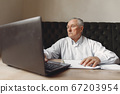 Old man sitting at the table and working with a laptop 67203954
