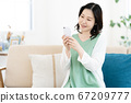 A middle woman who operates a smartphone in the living room 67209777