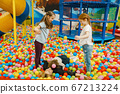 Children with mother lying among colorful balls 67213224