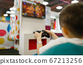 Boy plays a game console in entertainment center 67213256