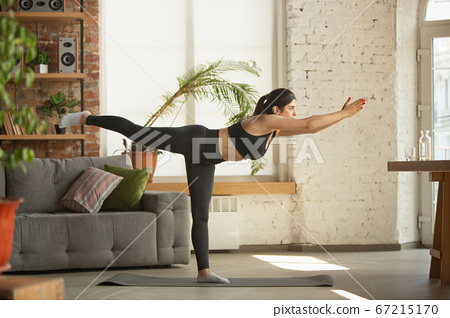 Sporty young muslim woman taking yoga lessons online and practice at home 67215170