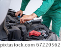 Professional mechanic hand providing car repair and maintenance service 67220562