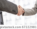 Male and female business partners shaking hands 67222981