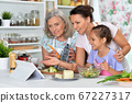 Smiling happy family cooking together at kitchen 67227317