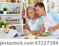 Portrait of family making fresh salad at kitchen 67227384