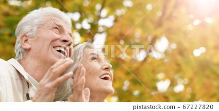 Portrait of smiling senior couple in autumn park 67227820