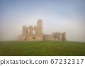 Old castle ruins in a dense fog 67232317