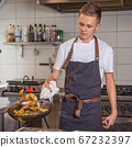 young chef prepares potatoes in a pan. Reversed by ejection 67232397